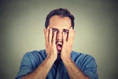 Wanhopige ongelukkige mens op grijze muurachtergrond Royalty-vrije Stock Fotografie