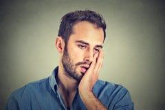 Wanhopige ongelukkige mens op grijze muurachtergrond Royalty-vrije Stock Afbeelding