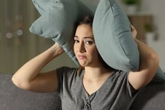 Wanhopige vrouw die oren tegen lawaai behandelen te beschermen stock afbeelding