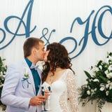 Właśnie zamężni buziaki trzyma szkła z szampanem Obrazy Stock