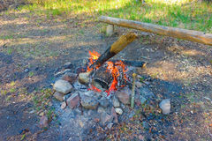 A waning campfire in a stone fire-pit Stock Images