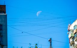 Waning moon caught on the wires royalty free stock photos