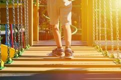 wankelende stappen voor kinderen in de openbare speelplaats met kid& x27; s been, zonlichteffect stock foto's
