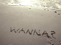 Wanna?. Suggestive message written in the sand. Part of my sepeia toned retired couple on the beach series. Keyword sereis1rc to see the entire series with Stock Images