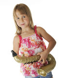 Wanna' Be Sax Player. A pretty young elementary girl happily holding a toy gold saxaphone.  On a white background Stock Image