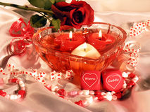 Wanna Cuddle 2. Heart shaped dish with three heart shaped floating candles. Romantic dice that say Wanna Cuddle royalty free stock photography