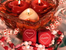 Wanna Cuddle (Closeup). Closeup of heart shaped floating candles in a heart shaped bowl.  Romantic dice that say Wanna Cuddle Royalty Free Stock Photo