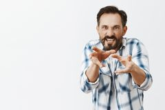 Wanna kill my mother-in-law. Portrait of annoyed and angry man with beard and dark hair, pulling hands towards. Camera to choke someone from anger and hate royalty free stock photos