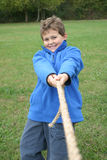 Wanna Play?. A smiling boy invites to a good game of tug-of-war. A great image for sports or use an illustration of the power struggle of parenting Stock Photos
