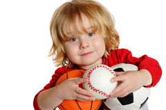 Wanna Play. Closeup of a young boy holding a basketball, baseball, and soccerball Stock Image