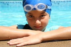 Wanna race?. Little girl, wearing a sporty bathing cap, looks over the poolside with a challenging look stock image