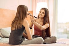 Pleasant teenage girl applying powder to her sisters face Royalty Free Stock Photo