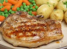 Wanne gebratenes Schweinekotelett mit Frühkartoffeln Stockfotos