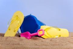Wanne, Schaufel und Flipflops auf dem Strand lizenzfreie stockbilder