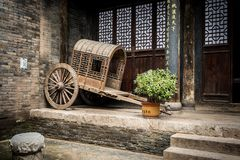Empty ancient Chinese cart resting against a brick wall stock images
