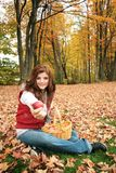 Want some apples?. Young woman sit in red leaves in a park with a basket with apple, offer an apple to somebody Royalty Free Stock Images