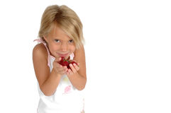 Want some fruit?. Little girl eats healthy fruit and chooses better snacks than sugar or candy. Teaching children about healthier diets. Child on white Royalty Free Stock Photos