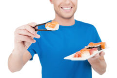 Want some sushi?. Cropped image of cheerful young man proposing sushi while standing isolated on white Royalty Free Stock Images