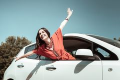 Happy young female person enjoying warm day. Want to fly. Cheerful brunette woman expressing positivity and posing on camera stock photos