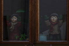 We want to get out of here. Two dolls stand at the window and wave Royalty Free Stock Image