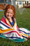 Want to get wet?. Little redheaded girl wrapped in towel with sprinkler in the background Royalty Free Stock Photos