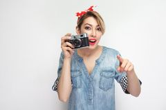 Want to make photoshout. Young blogger girl in casual denim shirt with makeup, red headband standing, holding retro camera and. Pointing finger to you. indoor stock photo