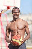 Want to play? Young african decsent men with naked torso holding. Want to play? Young african decsent man with naked torso holding a ball in his hand with a stock photos