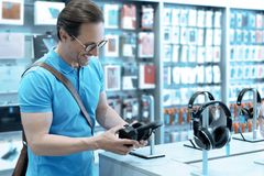 Fanatic music lover choosing headphones. Want to try it. Attractive brunette bowing head and keeping smile on face while looking at accessories Stock Photos