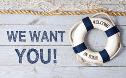 We want you. In graphic block text on weathered boards with fishing net, rope and lifebuoy Royalty Free Stock Image