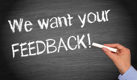 We want your feedback concept. Hand of person writing we want your feedback on blackboard; business concept stock image