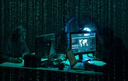 Wanted hackers coding virus ransomware using laptops and computers. Cyber attack, system breaking and malware concept. royalty free stock photography