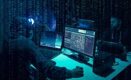 Wanted hackers coding virus ransomware using laptops and computers. Cyber attack, system breaking and malware concept. Wanted hackers coding virus ransomware stock photography