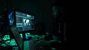 Wanted hackers coding virus ransomware using laptops and computers in the basement. Cyber attack, system breaking and