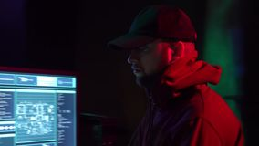 Wanted hackers coding virus ransomware using laptops and computers in the basement. Cyber attack, system breaking and. Malware concept stock footage