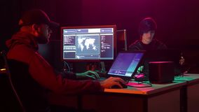 Wanted hackers coding virus ransomware using laptops and computers. Cyber attack, system breaking and malware. Wanted hackers coding virus ransomware using stock video