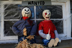 Wanted Halloween Monsters Gang. Halloween Decoration, Dolls of Scarecrow Killer and Zombie in front of window of old house covered with spider web under sign Royalty Free Stock Image