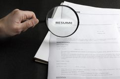 Lot of resume applications on the black desk,HR holding magnifying glass,concept of searching professional employees. Wanted new employees.Free vacancy concept stock image