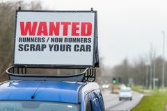 Wanted Runners Non Runners Scrap Your Car sign on car roof next to UK motorway.  stock photo