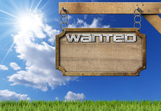 Wanted - Wood and Metal Sign with Chain. Wooden sign with planks and metal frame with text Wanted. Hanging from a metal chain on a pole on blue sky with clouds Stock Images