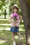 She wants someone to give as a gift, a bouquet of flowers. Little cute girl in a skirt with a hat holding a bouquet of flowers and waiting for someone Stock Photos