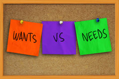 Wants vs Needs. The words wants vs needs written on sticky colored paper over cork board royalty free stock images