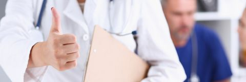 Wapen bevestigt de vrouwelijke artsenhand die o.k. tonen of Royalty-vrije Stock Afbeelding