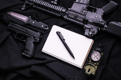 Wapen, notitieboekje, pen, mes en kompas op zwarte stof Royalty-vrije Stock Fotografie