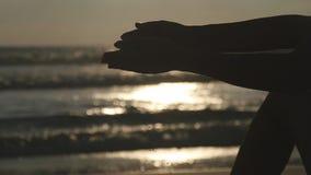 Wapen van het jonge vrouw spelen met zand Vrouwelijk hand gietend overzees zand door haar vingers bij zonsondergang tegen een oce stock footage