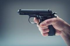 Wapenkanon De hand die van mensen een kanon houden 9 mmpistool Stock Afbeelding