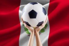 Wapens die bal met vlag van Peru houden Stock Foto's