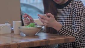 Wapens van jonge onderneemster die een smartphone voor mededeling gebruiken Zij zit bij de lijst in koffie en eet een salade stock footage