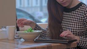 Wapens van jonge onderneemster die een tablet voor mededeling gebruiken Zij zit bij de lijst in koffie en eet een salade stock footage