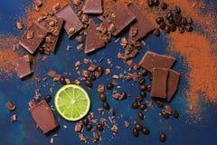 Wapni plasterek z kawałkami czekolada i smażyć kawowe fasole na błękitnym tle na widok fotografia stock