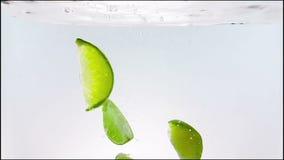 Wapno plasterka owocowego pluśnięcia spada puszek w białego koktajl i wodę pije szkło, strzał w zwolnionym tempie na białym tle zbiory